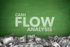 Cash flow analysis on green blackboard with dollar bills